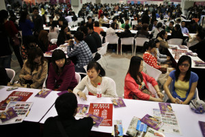Women sit and talk as they wait to meet men during a matchmaking event in Shanghai